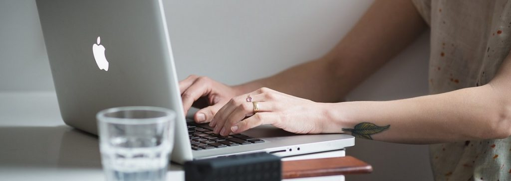 Woman typing at a laptop